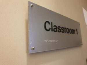 tactile door sign with raised lettering and braille